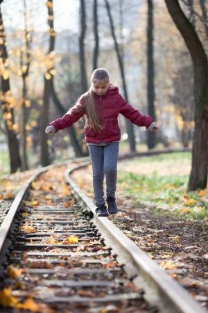 Fille en équilibre sur le rail dans le parc automne
