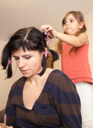 Cute little girl making her mother funny haircut photo