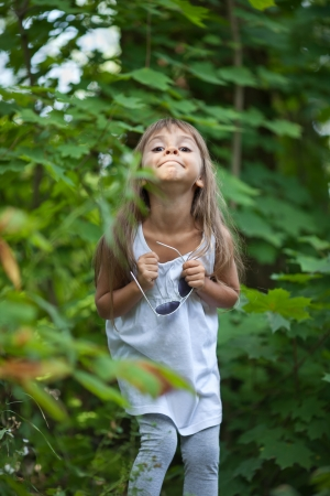 sidewards: Little girl grimacing in the forest
