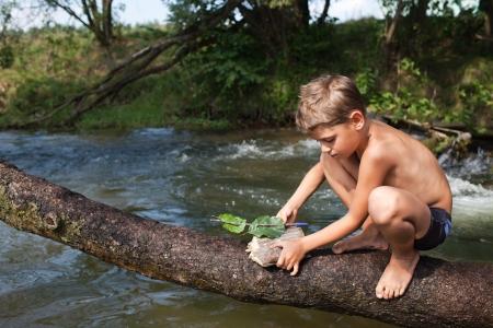 Boy fabrication d'un bateau d'écorce et de feuilles Assis sur un tronc d'arbre sur l'eau