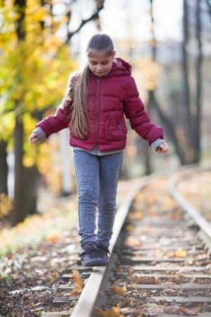 Fille en équilibre sur le rail à l'automne parc Banque d'images