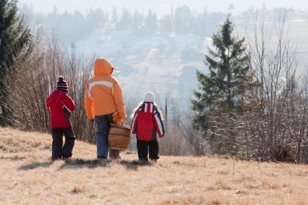 niños caminando: Family ir con la cesta de picnic en las montañas de invierno Vista trasera
