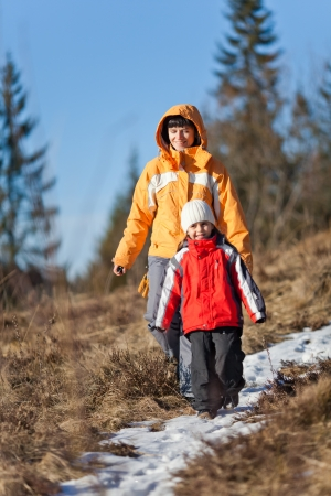 Daughter and mother hiking a snow covered path in the forest late winter