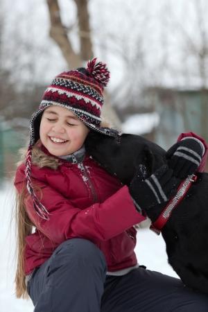 Portrait d'une belle jeune fille à l'extérieur en hiver obtenir un baiser d'un chien labrador noir naturel moment, candide Banque d'images