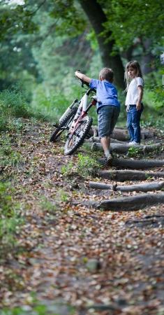 Los ni�os que caminan en ni�o peque�o bosque caminando con su bicicleta en lo alto de la colina Foto de archivo - 18541445