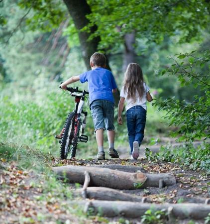 Les enfants marchent dans la forêt garçon Llittle marche avec son vélo en haut Banque d'images