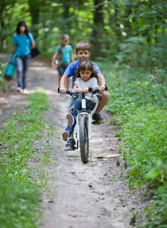 Two children share a bicycle as they travel on forest  Family on background photo