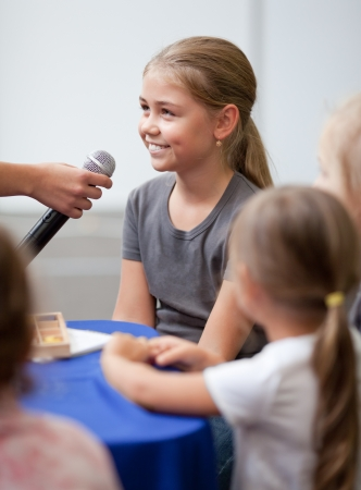 Smiling ten year old girl speaks into handheld microphone  A woman