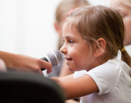 Smiling five year old girl speaks into handheld microphone  A woman