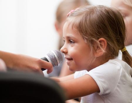 Sourire fille de cinq ans parle dans le microphone de poche Une femme