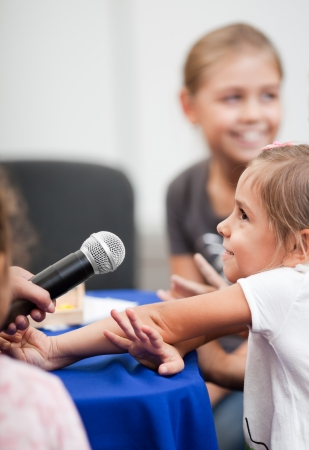 Smiling five year old girl speaks into handheld microphone  A woman photo