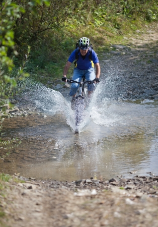 A mountain biker speeding through a muddy stream Фото со стока