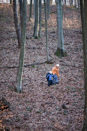 Mother and daughter are walking down a hill in forest photo