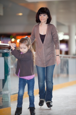 Action shot of beautiful woman teaching her daughter how to ice skate photo