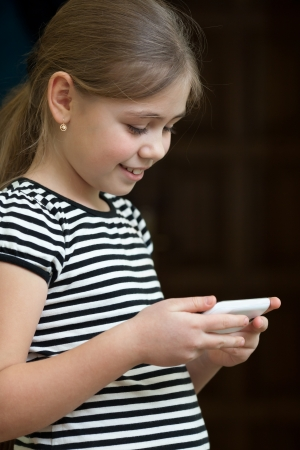 pre adolescence: Little girl reading sms on mobile phone and smiling