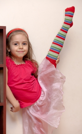 Smiling little girl stretching her leg in the home photo