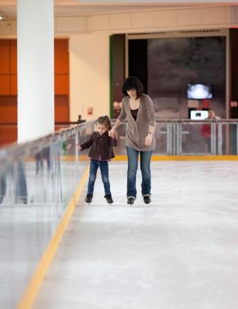 Photo d'action de belle femme enseigne à sa fille comment patin à glace