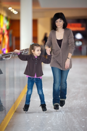 Action shot of beautiful woman teaching her daughter how to ice skate