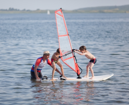Two little boys try to balance on windsurfing board  with child's sail.  Next to them is male instructor