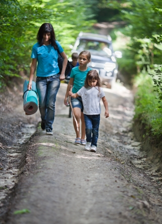 Mother and her three children hiking on road in woods. Car on background. photo