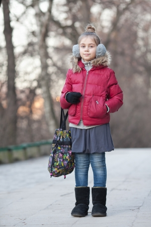 A beautiful little girl in fur headphones with bag photo