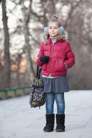 Une belle petite fille dans un casque de fourrure avec sac
