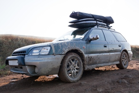 caked: Car, loaded with windsurfing gear on top, splattered and caked with mud  Wet clay road  Sun behind the car Stock Photo