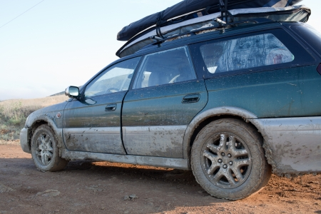 caked: Car, loaded with windsurfing gear on top, splattered and caked with mud  Wet clay road