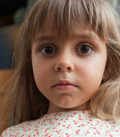 A beautiful little girl gazing intently at you photo