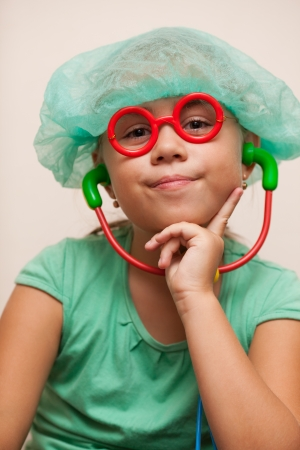 stethoscope girl: Cute smiling little girl with toy glasses and a toy stethoscope in doctor