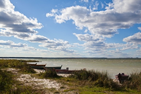 Lake shore with lonely boats at windy and sunny day with beautiful sky photo