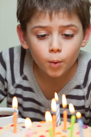 Jeune garçon soufflant des bougies sur le gâteau d'anniversaire