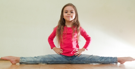 Five year old girl do leg-split (Front splits) smiling wearing casual clothes photo