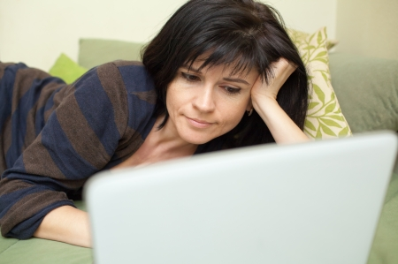 Woman at home lying on sofa and working with laptop Stock Photo - 23938708
