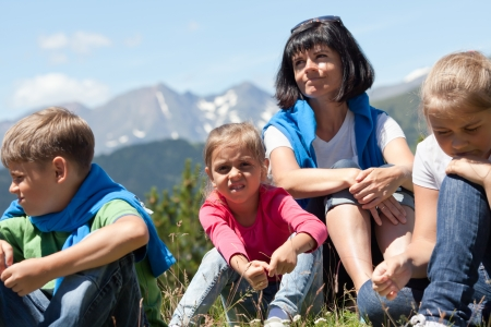 Portrait of a mother with three children outdoors the summer