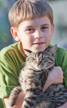 Tabby cat cuddles with nine year old boy