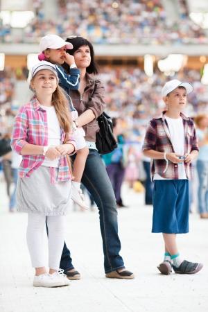 trois enfants: Concert au stade. Les spectateurs sont sur le terrain. Famille avec trois enfants pr�s