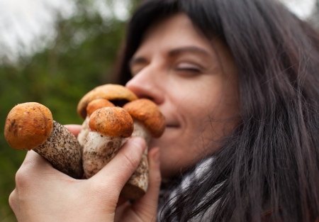 Adorable woman sniffing fresh mushrooms. Close up Фото со стока