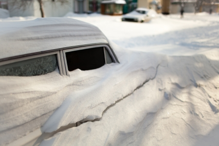 stuck up: White old car covered with snow after the winter blizzard