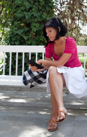 Woman reading a digital book on a bench at the park photo