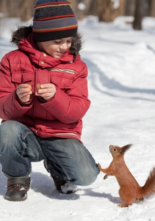 Cute little boy feeding squirrel at winter park photo