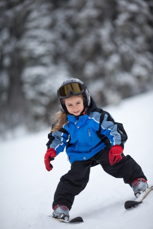Happy little girl having fun skiing down the ski slope photo