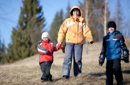 Mother, daughter and son hiking in the forest late winter photo