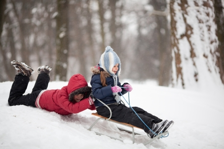 Two little children having fun using sled in a park
