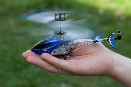 Mini RC helicopter rises over hand Фото со стока