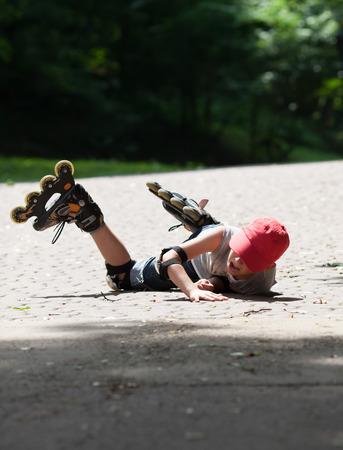 어린 소년 롤러 스케이트는 우연히 빠진다. 그는 고난을 당하고 고통의 얼굴을 보입니다. 스톡 콘텐츠