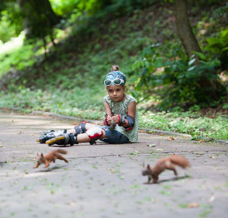 roller blade: Cute little girl with roller blade and squirrels at park