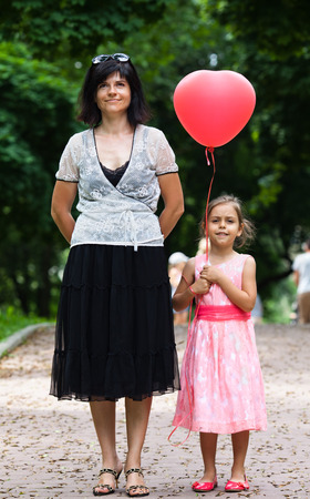 Portrait of a happy mother and daughter with balloon together in park photo