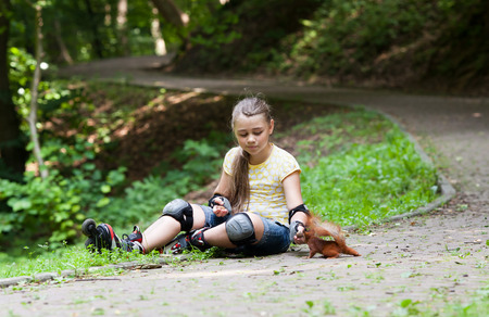 roller blade: Cute little girl with roller blade and squirrel at park Stock Photo