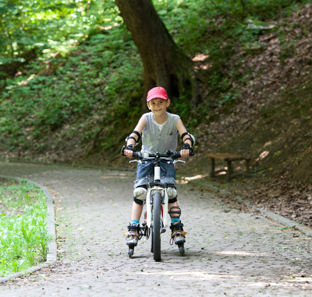 simultaneously: Little boy on roller skates and bike simultaneously